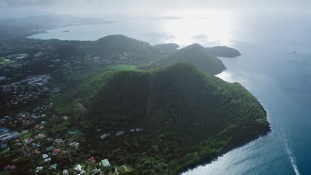Aerial shot of a wooded mountain on the coast of the blue sea and the city at the foot on a cloudy day (Saint Lucia)