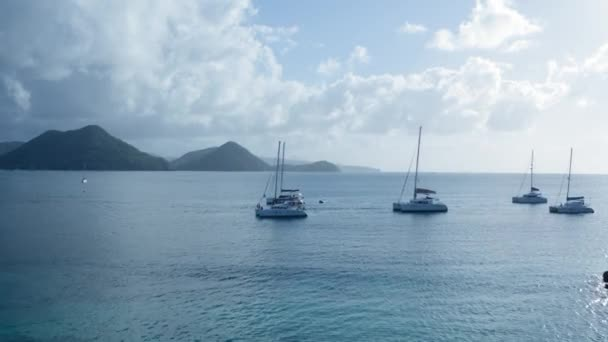 Drone camera moves through yachts to the sea and approaches the mountainous shore (Saint Lucia)