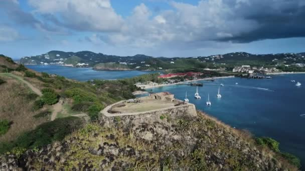 Aerial shooting of Fort Rodney on a mountain, an island, a city, mountains and yachts at at Rodney Bay, Saint Lucia