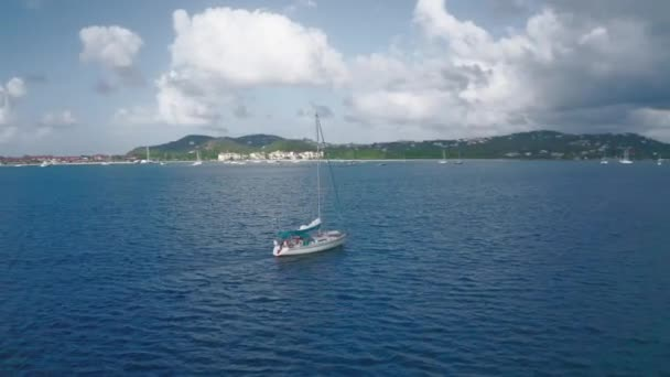 Drone whirls over a yacht in the sea on the horizon shore with hills and clouds (Saint Lucia)