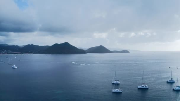 Aerial footage of water bike circling among yachts in the sea, on the horizon mountains, city and fog (Rodney Bay, Saint Lucia)