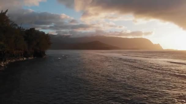 Drone shoots purple sunset over the waves, black mountains in the clouds on the horizon (Kauai, Hawaii, USA)