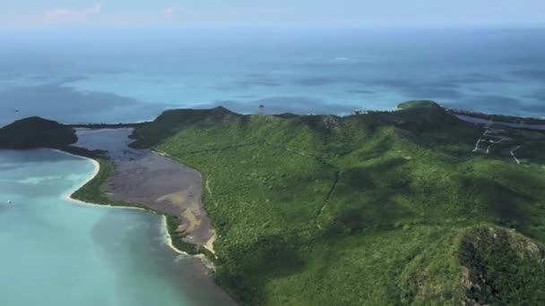 Drone shoots a green island with hills and a serpentine road, around the azure sea at Antigua and Barbuda