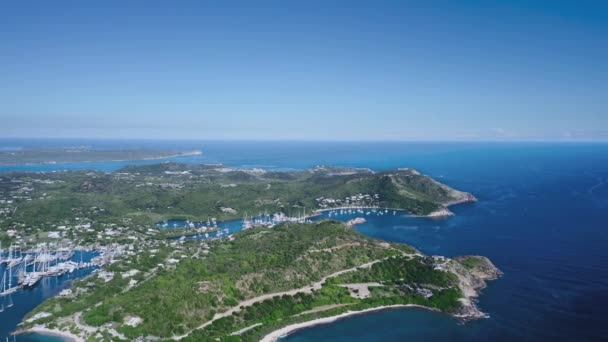Drone shoots a hilly island with dense vegetation and marina with white yachts from a birds eye view Antigua and Barbuda