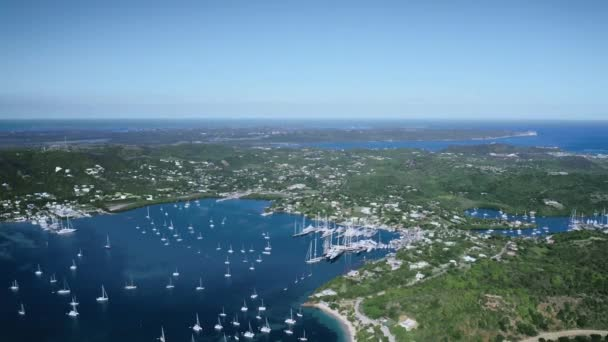 Aerial shot of the bay with white yachts, a city and a dense forest Antigua and Barbuda .