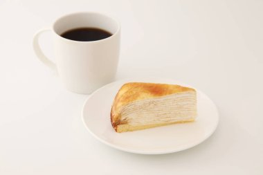 hot coffee with Mille crepe french cake on a plate on white background