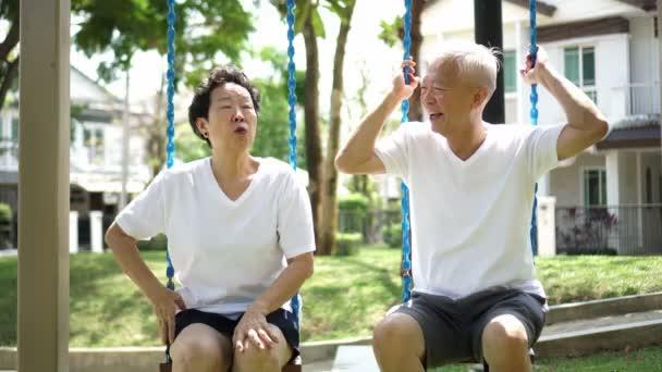 Asijské starší pár mluvit relaxovat v parku swing fun