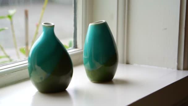Dvě zelené zen keramické glazované vázy na okenním parapetu