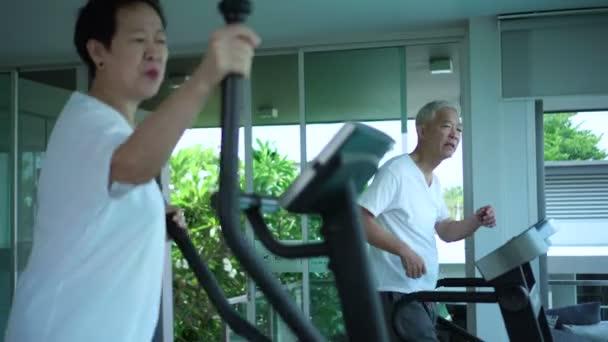 Asijské starší pár cvičení v tělocvičně, kolem se sklem a příroda