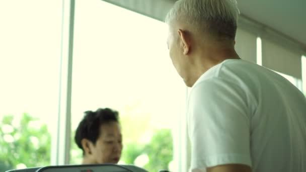 Ázsiai idősebb pár gyakorlása, a tornaterem, az üveg és a természet körülvevő