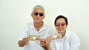 Asian eldery couple happy wealthy holding Japanese Yen money