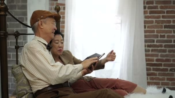 Asian elderly couple using smartphone in vintage home