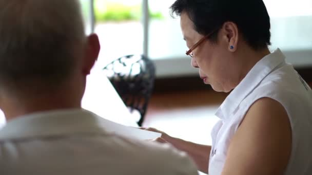 Asian Senior Couple Discuss News Article From Magazine Study And Learn Things