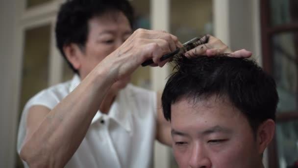 Asian family motherdoing lockdown home haircut barber for family memeber during quarantine time