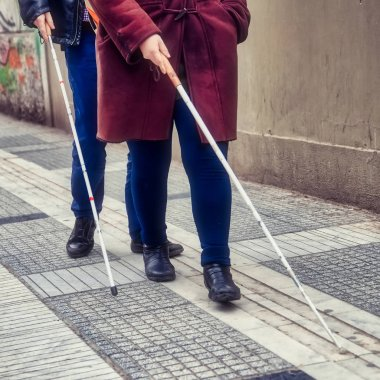 blind man and woman walking on the street using a white walking