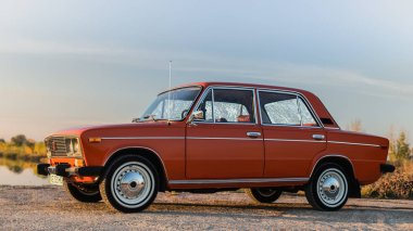 PERESHCHEPINO, UKRAINE - OCTOBER 12, 2014: Zhiguli VAZ 2106 original orange, released in the USSR in 70's. Car parked on the side of the road in the middle of sunny day without cars nearby