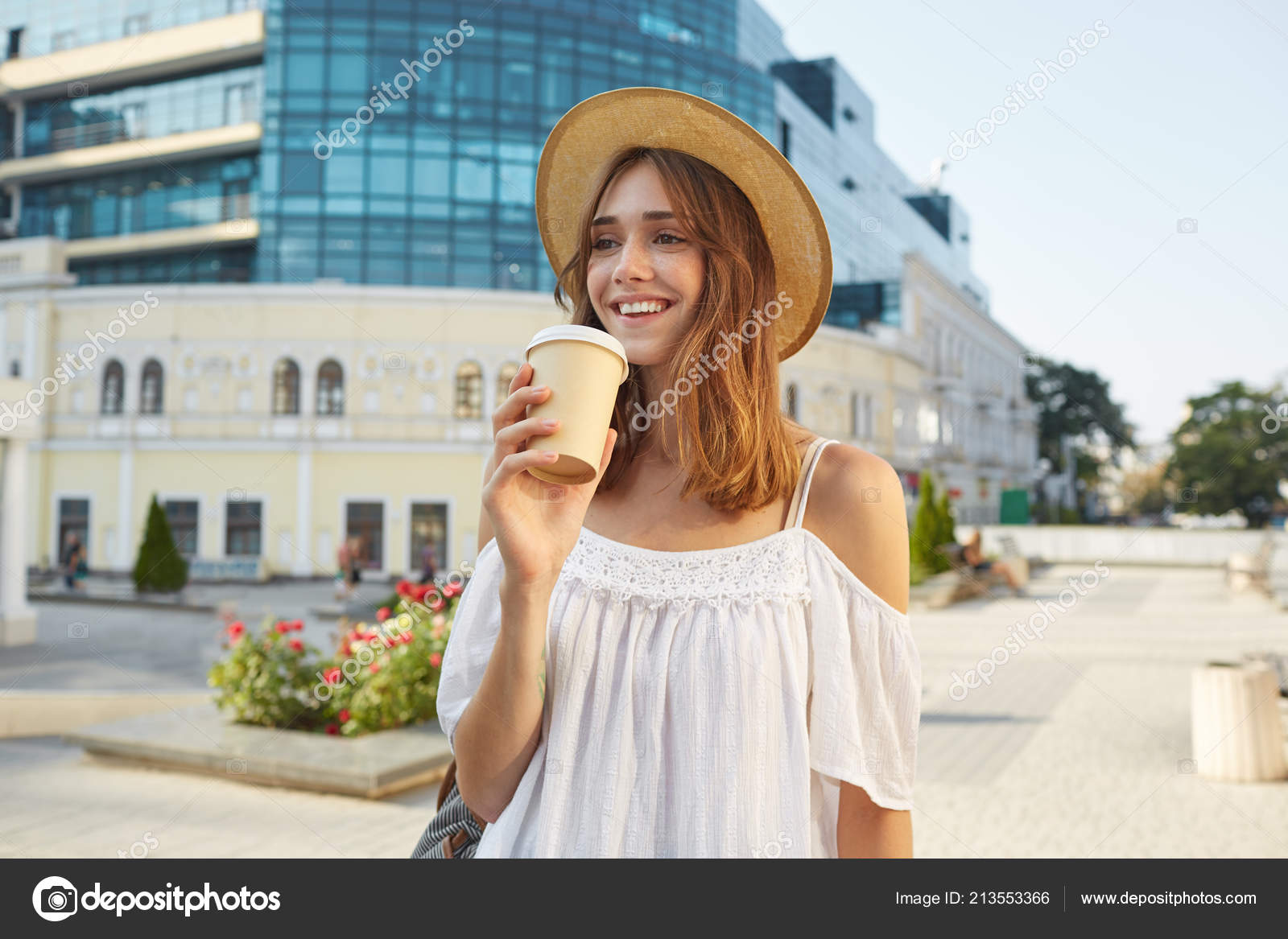 5de3c8ee2 Outdoor portrait of happy cute young woman wears stylish summer hat and white  dress, feels relaxed, smiling and drinking takeaway coffee on the street in  ...