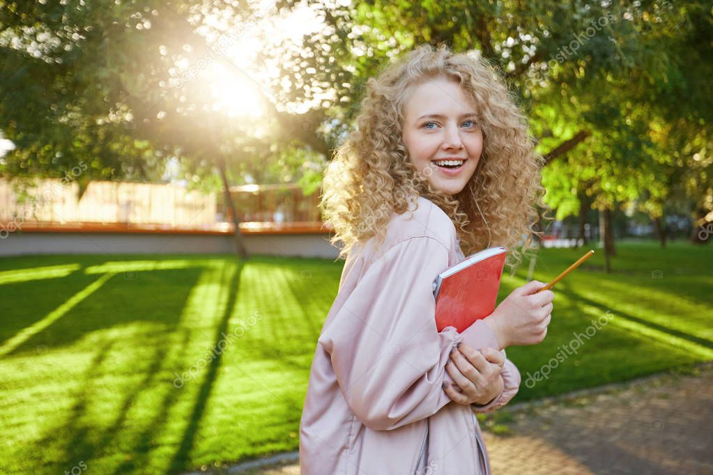 Young blonde-hair student walks through the park, with a red notebook and a pencil in hands, headphones in her ears with favorite music, looks into the camera and smiles