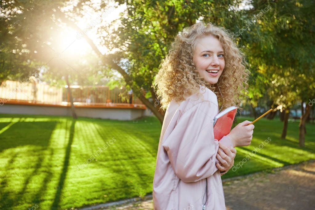 Beautiful curly hair young girl passes by with a red notebook and a pencil in hands, headphones in her ears with favorite music, looks into the camera and smiles, park background.
