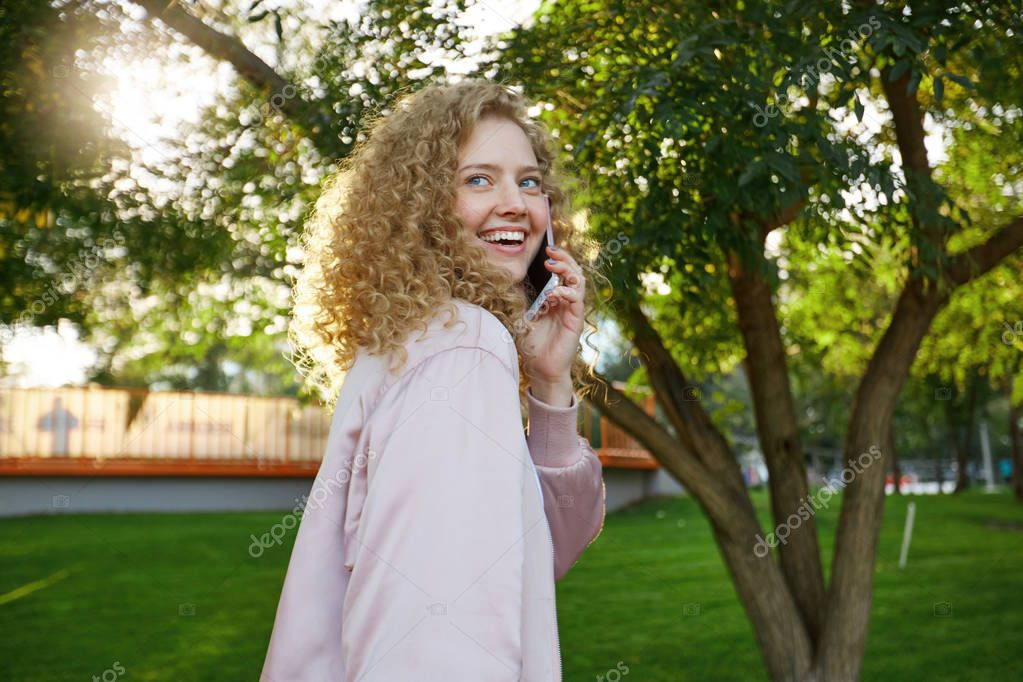 Outdoor photo of beautiful attractive charming curly hair young girl passes by, speaking with someone on phone, looks around and smiles, park background.