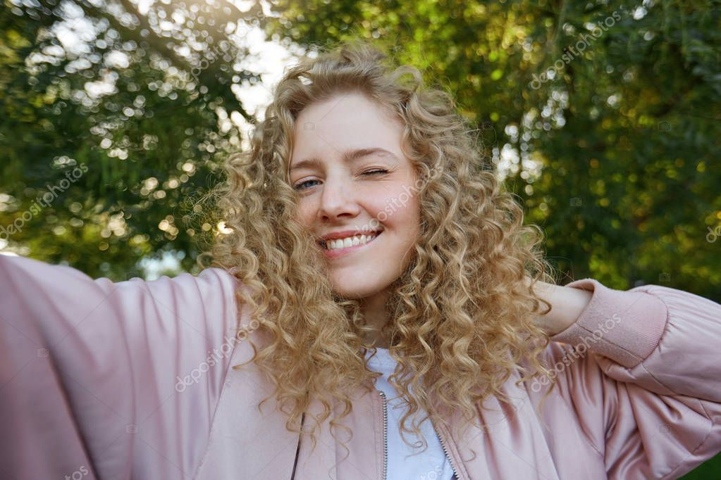 Funny attractive pretty blonde girl with curly hair, making selfie on own phone for social networks, winks, bit her lower lip, flirts, nature background