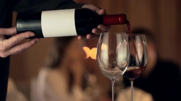Muž nalévá červené víno do sklenic