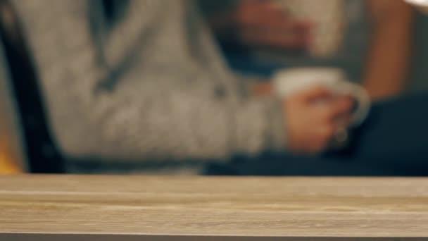 Egy férfi kézzel tett egy kávéscsészét az asztalra..