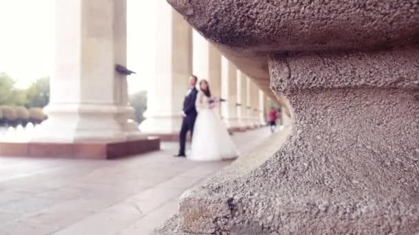 nevěsta a ženich stojí mezi sloupy v rozmazané mělké hloubce pole
