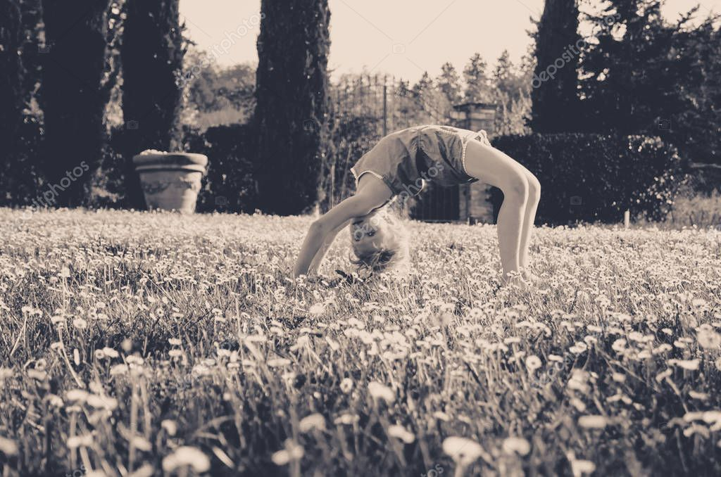 girl with acrobatic posture in green meadow full of flowers monochrome retro