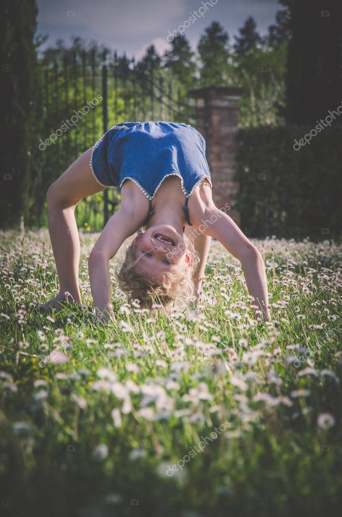 girl with acrobatic posture in green meadow full of flowers
