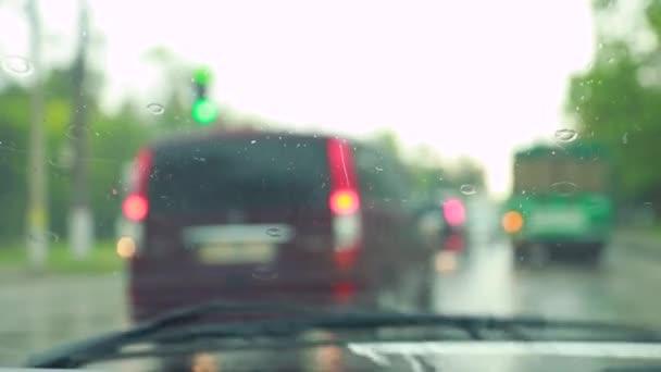 Auto se pohybuje po městě v dešti