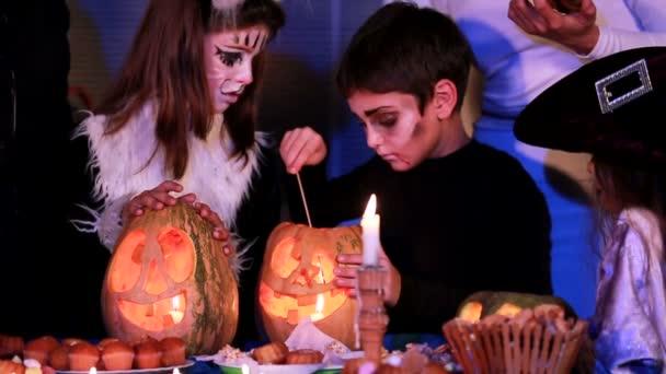 Děti v oblecích uhasí svíčky v dýních. Zpomalený pohyb.