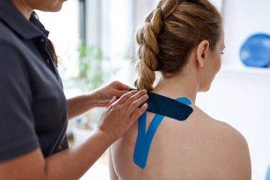 Chinese woman massage therapist applying kinesio tape to the shoulders and neck of an attractive blond client in a bright medical office