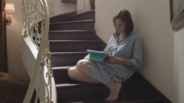 Young brunette women sitting on wooden stairs and working on tablet. Female adult talking by tablet in classic interior