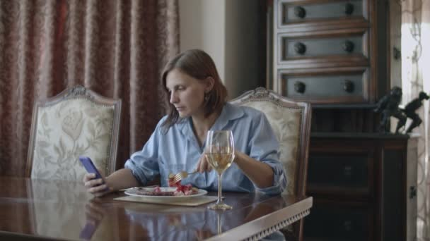 Brunette women having meal with glass of white wine and talking by phone
