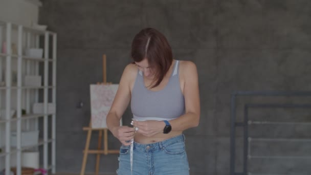 Young woman admiring the result of weight loss while wearing old jeans in bedroom. Happy female taking picture of her belly after you lost weight.