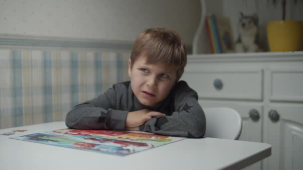 Autistic kid completing last pieces of jigsaw puzzle on the table in slow motion. Child with autism solving puzzle jigsaw. Autism awareness