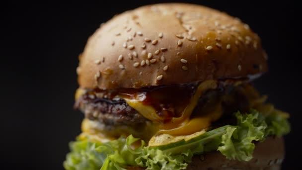 Mňam burger s dvojitým hovězím kotletem, roztaveným sýrem, salátem a zeleninou rotující na tmavém pozadí ve zpomaleném filmu.