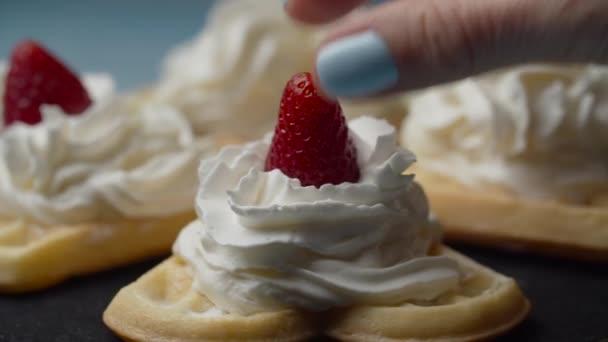 Hausgemachte Waffeln mit Schlagsahnebelag rotieren. Frische Erdbeeren auf weißen Sahnewaffeln in Zeitlupe.