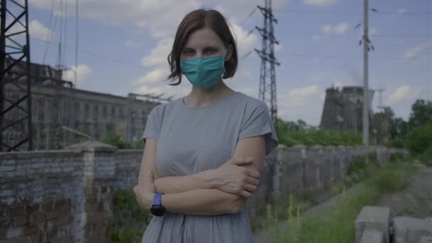 Young woman in facial protective mask standing in industrial city district on sunny day. Woman in mask alone on the street.