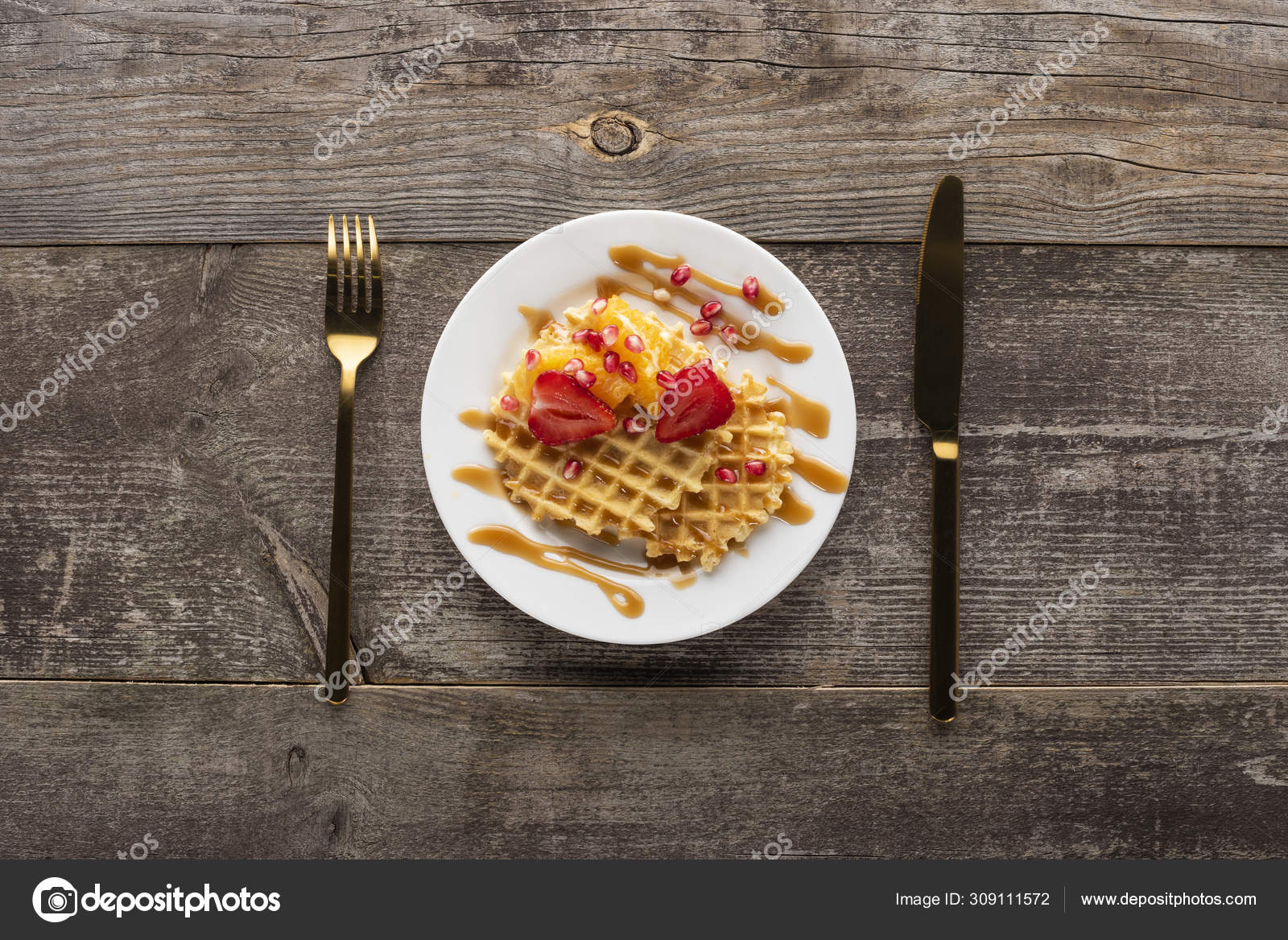 Waffles with strawberries on a white plate on a white background with golden fork and knife