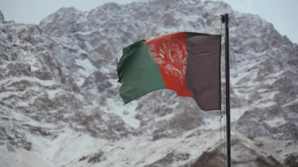 afghanistan flag waving in the wind against the backdrop of snowy mountains