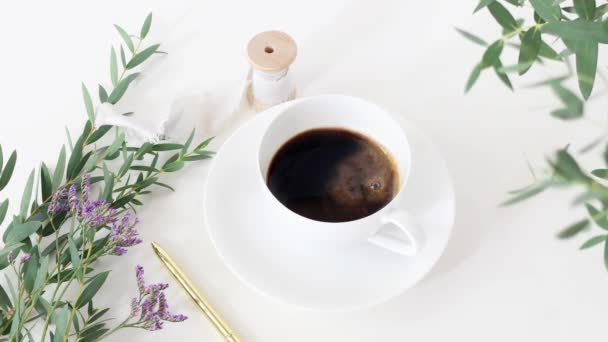 Cinemagraph. Cup of coffee, wedding bouquet, silk ribbon and golden pen on white table background. Eucalyptus branches moving in breeze. Feminine breakfast desktop composition. Top view. Loopable.