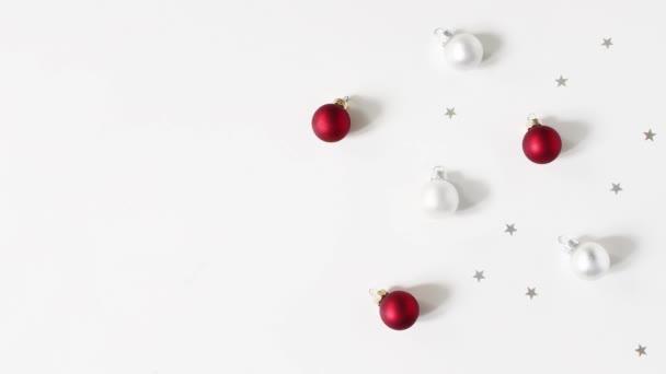 Weihnachten-Komposition. Noch und weißen Tabellenhintergrund rote und weiße Weihnachtskugeln, Christbaumkugeln und silbernen Sternen Konfetti Dekoration weitergehen. Flach legen, Top Aussicht. Winter Patttern. Endlos wiederholbar HD-Filmmaterial.