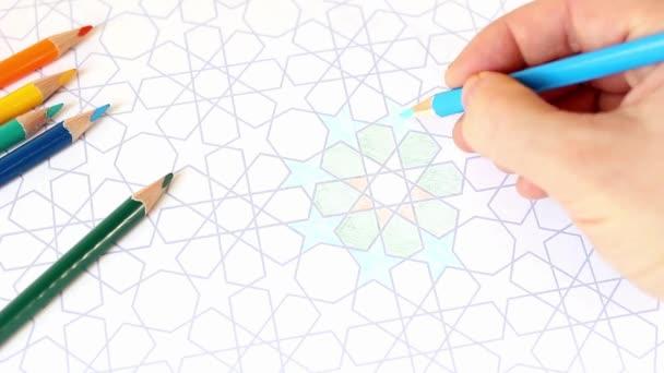 Polárszűrő az emberi kéz, rajzolás, színezés dekoratív arab kimono geometriai csillagok. Összetétele az asztalon színes ceruza. Művészi koncepció. Ramadan Hd felvétel.
