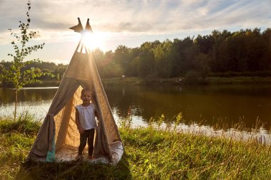 Girl at sunset in nature. Wigwam by lake. New home in hut. CHILDRENS GAMES.
