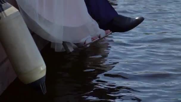 Lábak a menyasszony és a vőlegény a mólón a víz közelében.
