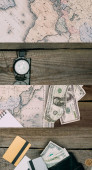 collage of map, compass, dollar banknotes and credit cards on wooden table, travel concept
