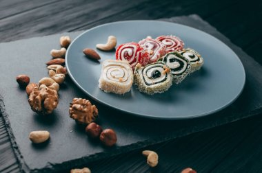 Traditional oriental sweets and nuts: hazelnuts, cashews on a dark wooden background. Turkish dessert is the Rakhat locus. View from above. Place under the text