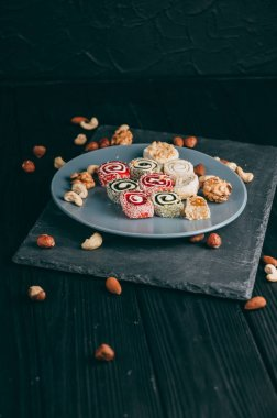 Traditional oriental sweets and nuts: hazelnuts, cashews on a dark wooden background. Turkish dessert is the Rakhat locus. View from above. Place under the text.
